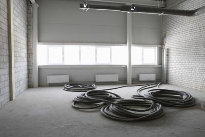 Picture of a fire department  building with hoses inside on a concrete floor.