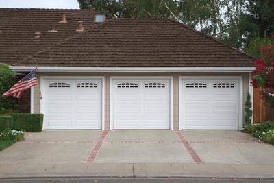 Picture of a three car garage with a concrete driveway with stamped red brick border in Nashua, New Hampshire.