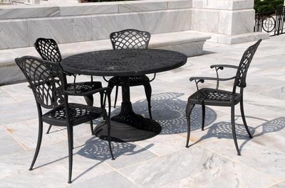 Picture of a stamped concrete patio with black iron table and chairs. Picture was taken in Nashua, NH